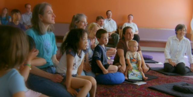 parents and kids sitting on floor listening to someone speak