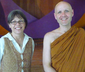 a woman and a monk smiling at camera